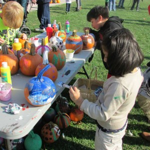 Children paint pumpkins, one of many activities and games kids could participate in. Photo by Philip Roth.